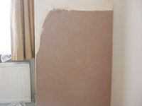 The Raynes Park Plasterer plaster repair to a lounge wall affected with damp in SW20